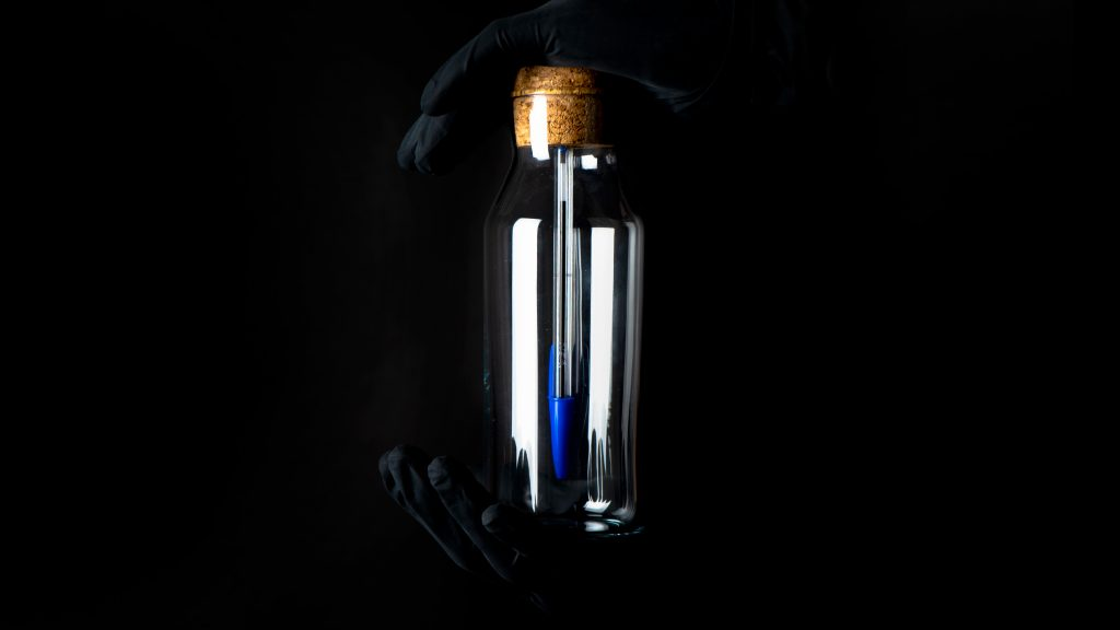 two hands with black gloves hold a bottles with blue bic pen inside